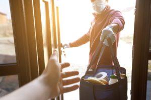 Sur cette image, on voit quelqu'un avec masque livrer les courses directement à la porte de quelqu'un d'autre