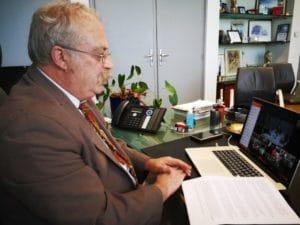 Sur cette photo, on voit Marc Vuillemot face à son écran d'ordinateur lors d'une visioconférence avec différentes associations d'élus et Président de la République